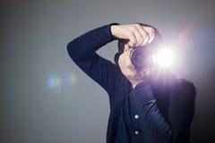 使用闪光,摄影师拍一张照片在演播室 库存照片
