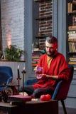 使用预言卡片的有胡子的占卜者坐在与蜡烛的桌 库存照片