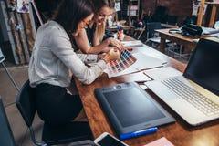 使用颜色样片的两位女性建筑师坐在有膝上型计算机的,图形输入板书桌在设计演播室 免版税图库摄影