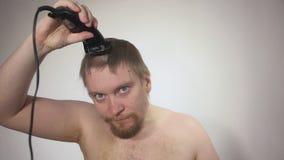 使用飞剪机的人刮在白色背景,射击特写镜头的头 股票视频