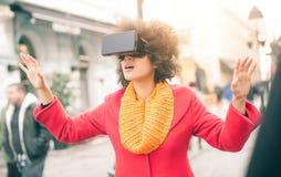 使用高科技虚拟现实玻璃的美丽的妇女室外 库存照片