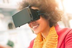 使用高科技虚拟现实玻璃的美丽的妇女室外 库存图片