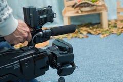 使用黑专业数字式摄象机的摄影师 室外设定和工作 免版税库存照片
