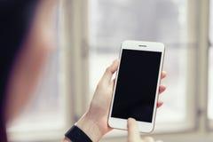 使用黑屏智能手机的妇女为应用 免版税图库摄影