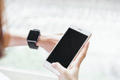使用黑屏智能手机的妇女为应用 免版税库存图片