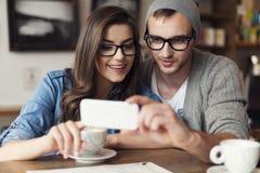 使用年轻人的夫妇移动电话 免版税图库摄影