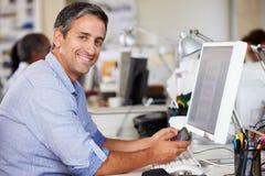 使用移动电话的人在服务台在繁忙的创造性的办公室 免版税库存照片