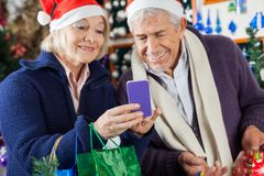 使用移动电话的资深夫妇在圣诞节商店 库存照片