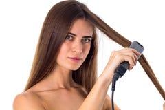 使用头发直挺器的妇女 免版税库存照片