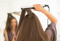 使用头发直挺器的少妇在卫生间 免版税库存照片