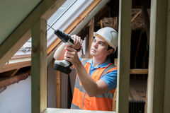 使用钻子的建筑工人安装替换窗口 库存照片