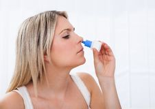 使用鼻孔喷射的妇女 库存图片