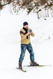 使用他巧妙的电话的滑雪者 库存照片
