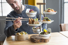 使用从有排列的服务器的筷子用餐顾客采取豆腐 库存照片