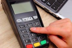 使用付款终端的妇女的手,进入个人身份证号码 免版税库存图片