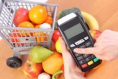 使用付款终端,水果和蔬菜,无钱支付购物,进入个人身份证号码 免版税库存照片