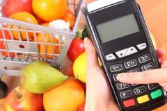 使用付款终端,水果和蔬菜,无钱支付购物,进入个人身份证号码 库存照片