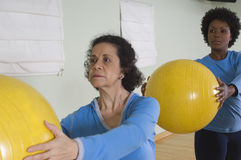 使用锻炼球的妇女在健身类 免版税库存照片