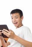 使用他的充满愉快的感觉的亚裔少年片剂 免版税库存照片