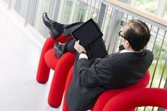 使用他的在一把红色扶手椅子的商人片剂 图库摄影