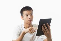 使用他的在片剂的亚裔少年手指 图库摄影