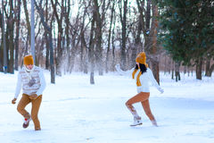 使用年轻的夫妇画象微笑和在冬天打雪仗 图库摄影