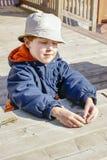 使用他的想象力的年轻男孩和使用与岩石和棍子 图库摄影