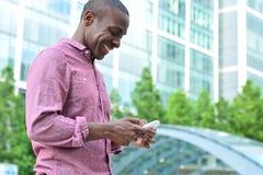 使用他的手机的微笑的人 免版税库存照片