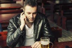 使用他的手机的英俊的人在餐馆 库存照片