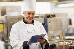 使用他的数字式片剂的厨师和看照相机 免版税库存图片