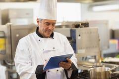 使用他的数字式片剂的厨师 库存照片