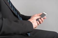 使用他的智能手机的商人 免版税库存图片