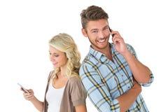使用他们的智能手机的有吸引力的夫妇 免版税库存照片