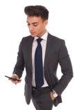 使用他的智能手机的年轻商人 库存图片