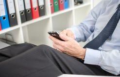 使用他的智能手机的轻松的商人 免版税库存图片