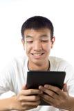 使用他的有微笑的亚裔少年片剂 免版税库存图片
