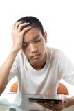 使用他的片剂的亚裔少年和感觉反感或d 图库摄影
