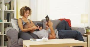 使用他们的片剂的黑夫妇在长沙发 免版税库存图片