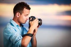 使用他的现代DSLR的英俊的年轻摄影师户外 免版税库存图片
