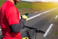 使用他的电话的愉快的骑自行车的人在冰岛 免版税库存照片