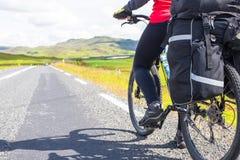 使用他的电话的愉快的骑自行车的人 冰岛山 免版税库存图片