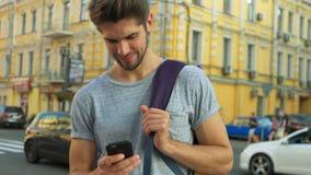 使用他的电话的游人在城市的中心 免版税库存图片