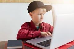 使用他的膝上型计算机和做他的家庭作业,一位小男小学生在红色衬衣和黑盖帽选址穿戴了在木桌上 一个聪明的男孩 库存图片