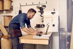 使用他的膝上型计算机的现代咖啡烘烤器沿着一现代roasti 免版税库存图片