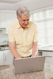 使用他的膝上型计算机的老人 免版税库存照片