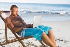 使用他的膝上型计算机的英俊的人,当放松在他的轻便折叠躺椅时 免版税图库摄影