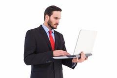 使用他的膝上型计算机的被聚焦的商人 库存图片