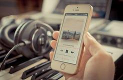 使用他的iPhone的音乐家听到在苹果计算机音乐的音乐 库存图片