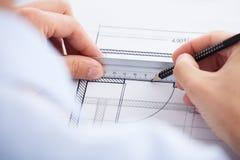 使用统治者和铅笔在图纸的建筑师 免版税库存图片