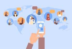 使用细胞巧妙的电话、回教人闲谈媒介通信社会网络阿拉伯男人和妇女的手在世界地图 库存照片